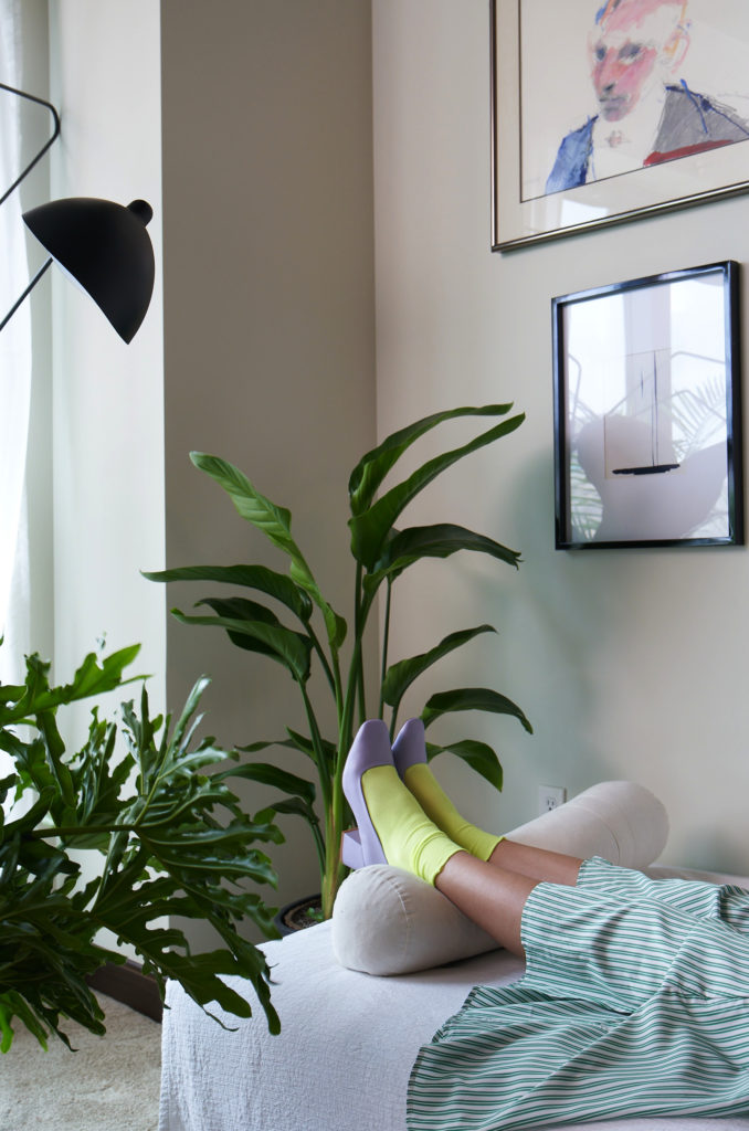 Woman laying on couch with plants
